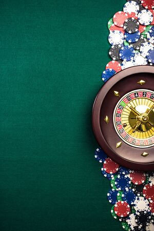 Casino Roulette Background with Roulette Drum,Casino Chips on Green Felt Table. Overhead View with Copy Space.
