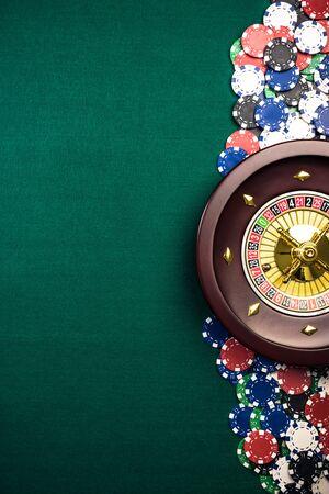 Fondo della roulette del casinò con il tamburo della roulette, fiches del casinò sul tavolo di feltro verde. Vista dall'alto con spazio di copia.