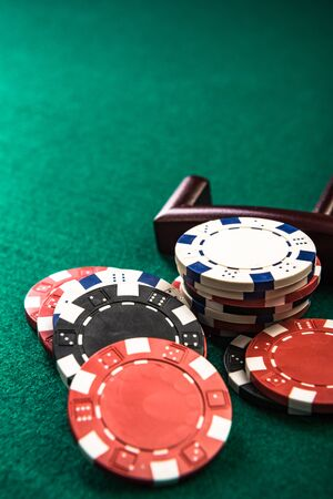 Poker or Roulette Casino Chips Close Up on Green Felt Casino Table.