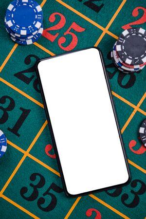 Mobile Phone White Screen on Green Felt Roulette Table. Online Casino Mockup Template. Reklamní fotografie