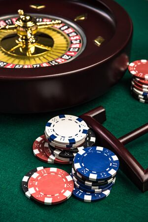 Wooden Roulette with Casino Chips on Green Felt.
