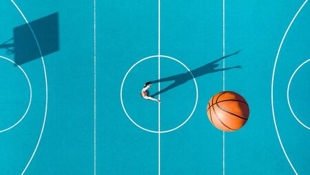 Basketball Player, Long Shadows on Basketball Court, Creative Visual Art, Aerial Image.