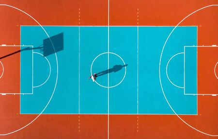 Basketball Player, Long Shadows on Basketball Court, Creative Visual Art, Aerial Image. Stockfoto