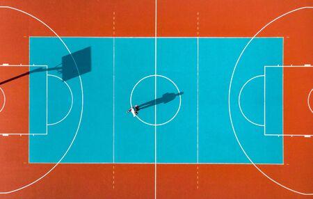 Basketbalspeler, lange schaduwen op basketbalveld, creatieve beeldende kunst, luchtfoto.