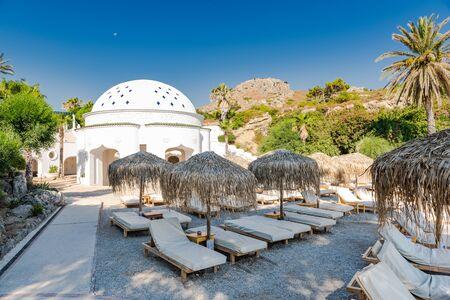 Kalithea Spring Therme Stühle am Strand mit Kieselsteinen und Bambusschirm, Rhodos, Griechenland.