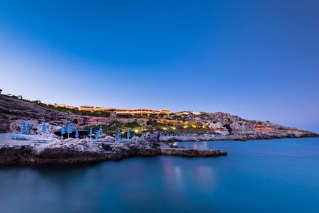 Twilight over Rocky Cliffs, Beach and Hotel Resort at Rhodes Island, Greece. 写真素材