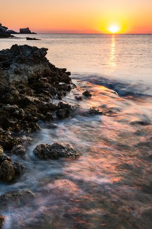 Sunrise at Rocky Beach in Rhodes,Greece. 写真素材 - 128779509