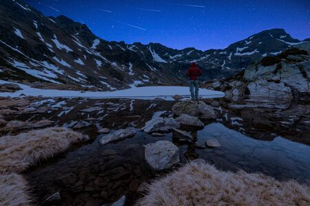 Man Watching Perseid MEteor Shower at Starry Night in High Mountains.