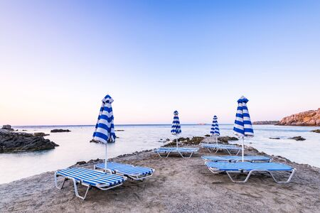 Colorful Sun Beds at Wild SEcret Beach at Sunrise in Rhodes, Greece.