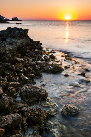 Sunrise at Rocky Beach in Rhodes,Greece. 写真素材 - 128779733