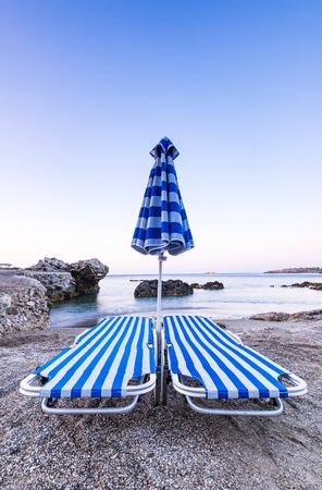 Typical Sun Beds at Pebble Wild Beach in Rhodes, Greece at SUnrise.