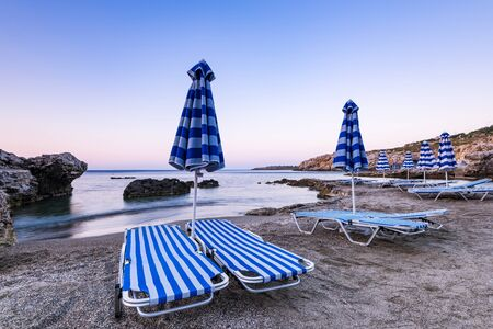 Umbrellas and Sun Beds at Pebble Beach at Sunrise, Rhodes, Greece. 版權商用圖片