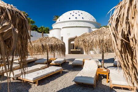 Kalithea Spring Therme Chairs on Beach with Pebbles and Bamboo Umbrella,Rhodes,Greece.