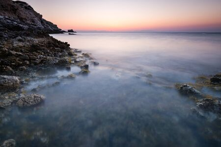Long Exposure Sunrise over Rocky Cliffs at Sea,Greece.