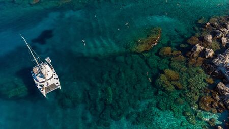 Aerial View over Yacht and People Swimming in Sea with Blue Clear Water.