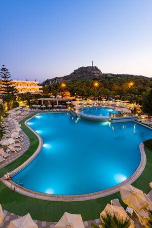 RHODES, GREECE - JULY 24, 2019: Kalithea Mare Palace, Luxury Hotel Resort with Swimming Poll Illuminated at Sunrise