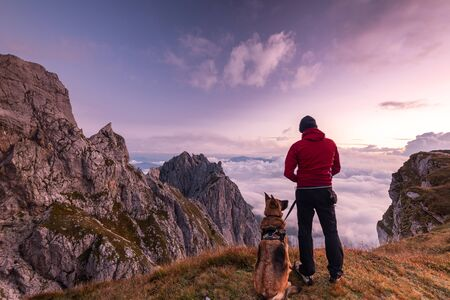 Adventure Man with Dog at High Mountains Peak at Sunrise. Togetherness and Friendship Concept. Stok Fotoğraf