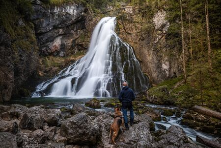 Adventure Man with Dog Hiking at Gollinger Waterfall in Austria. Stok Fotoğraf