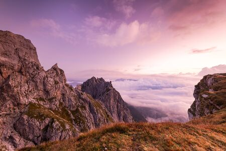 Breathtaking Sunrise at Mountains Peaks above Clouds. Pink Colors at Fall Season. Archivio Fotografico - 131793611