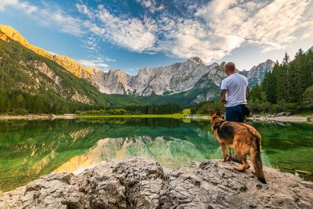 Tattoed Man with Dog Looking at Beautiful Lake and Mountains. Outdoor Active  Lifestyle, Adventure Concept. Archivio Fotografico - 131792621