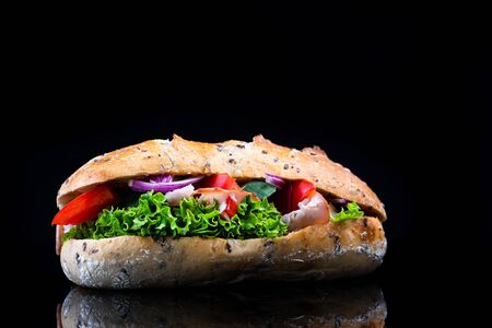 Sandwich with Ham and Vegetables. Studio Shot on Black Background. Stockfoto