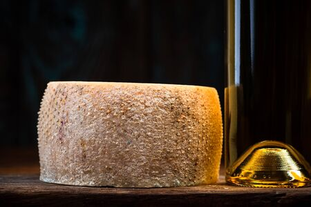 Hard Cheese Wheel Matured in Diary Cellar with White Wine Bottle. Local Traditional Produce. Zdjęcie Seryjne