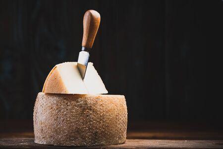 Pieza cortada de la rueda entera de queso curado. Productos alimenticios tradicionales.