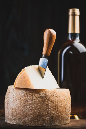 Piece Cut from Whole Matured Cheese Wheel. Traditional Food Produce.