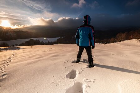 Outdoor Adventure. Active Man Standing in Deep Snow in Mountains at Sunrise.