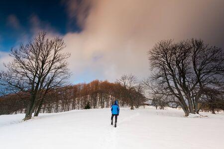 Adventure Outdoor. Active Man Walking in Snow at Winter Season.