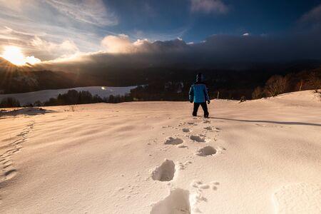 Outdoor Adventure. Active Man Walking in Deep Snow in Mountains at Winter. Sunrise . Reklamní fotografie