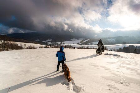 Active Couple Man and Dog Walking in Deep Snow. Outdoor Adventure. Reklamní fotografie