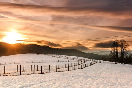 Beautiful Sunset over Snow Covered Farmland and Fields in Bieszczady, Poland.