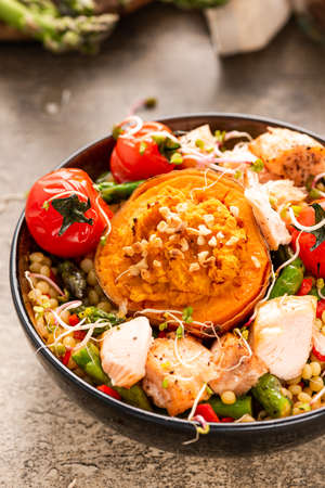 Stuffed Sweet Potato with Couscous and Vegetables in Bowl. 免版税图像