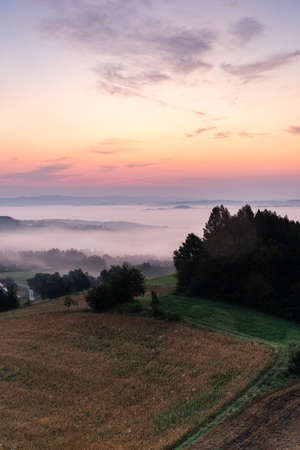 Countryside and Meadows in Morning Fog and Mist at Beautiful Sunrise.