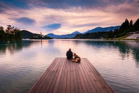 Man and Dog at Lake Bled,Slovenia. Real Friends Couple, Togetherness and Friendship Concept. 免版税图像