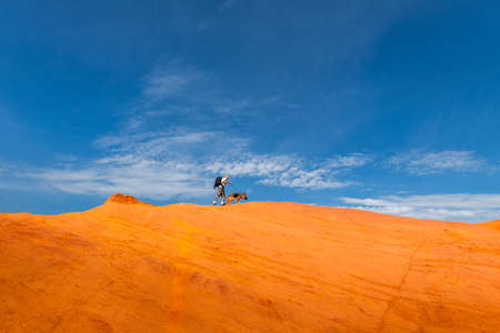 Man Walking with Dog on Edge of Red Mountains at Blue Sky.