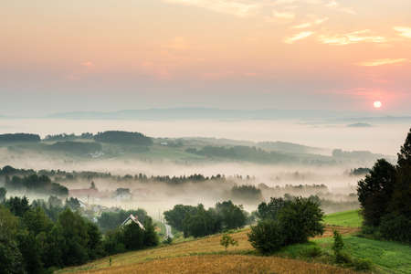 Rolling Hills in Morning Fog at Sunrise in Coutryside in Poland.