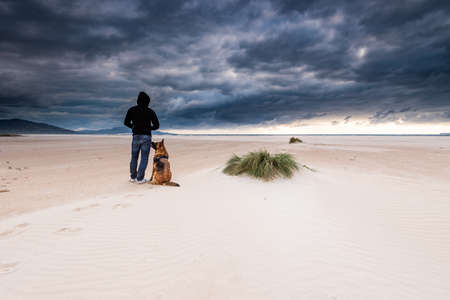 Man with Dog on Remote Beach. Social Distancing and Adventure in Pandemic New Normal times.