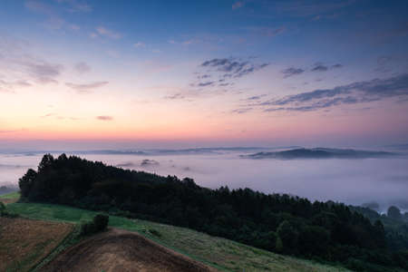 Beautiful Morning at Countryside. Rolling Hills in Morning Fog. Pink Sky. Blue Hour.