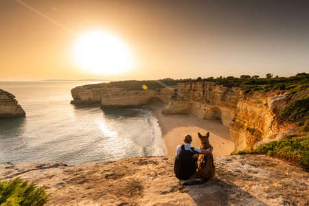 Friendship and Togetherness Concept. Man and Dog Looking at Sunset at Sea Cliffs in Portugal.