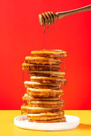 Pancakes with Honey on Colorful Bright Background. Graphic Food Studio Photo.