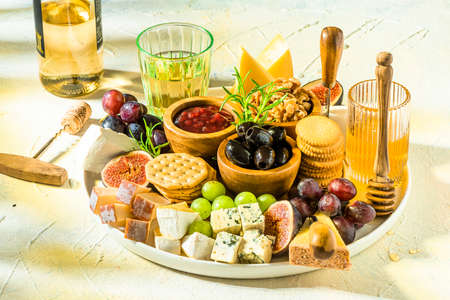 Cheese Platter or Cheese Board with Fruits, HErbs, Honey and Crackers. 免版税图像
