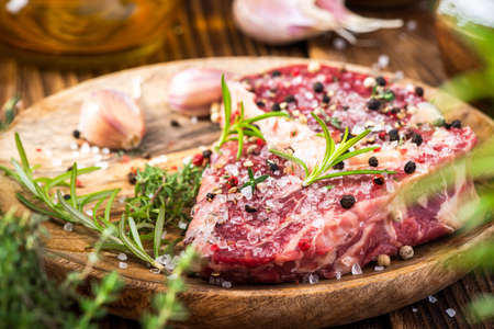 Beef Steak Meat on Wooden Plate with Herbs and Spices.