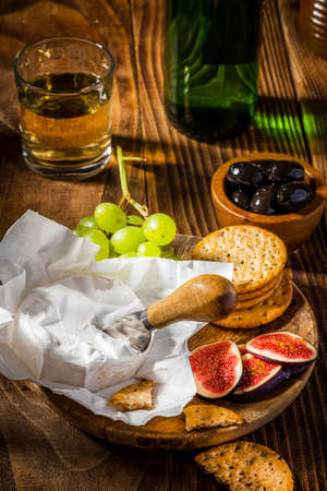 Camembert Cheese Serwed with Fruits and Wine on Wooden Table. 免版税图像