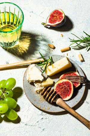 Cheese Appetizer with Figs and Grapes on Table.