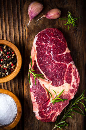 Uncooked Beef Steak Meat on Wooden Board. Top Down View. 免版税图像