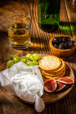 Camembert Cheese on Plate with Figs and Grapes Served with Wine.