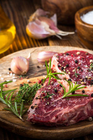 Fresh Raw Meat on Wooden Plate. Beef Steak Cut with Spices and Herbs.