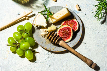 Cheese with Fresh Figs, Grapes, Honey and White Wine 免版税图像